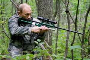 Putin aims a tranquilizer gun at a tiger at a nature reserve. Photo from  premiere.gov.ru.